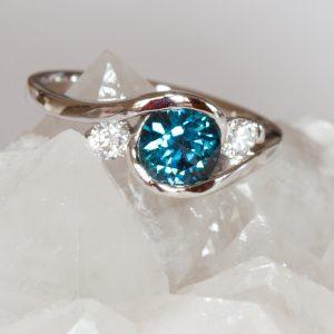Round teal sapphire and diamond swirl ring